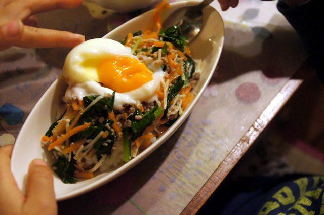 キットオイシックス(kit oisix)のミールキット「ジューシーそぼろと野菜のビビンバ」乗せた温泉卵が割れたおいしそうな画像